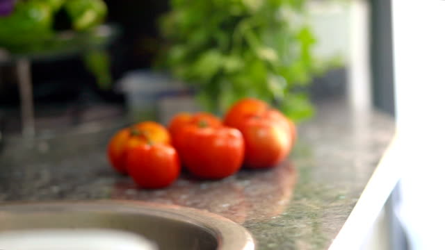 stockvideo's en b-roll-footage met close-up of a hands putting a salad bowl with tomatoes on the kitchen counter - alleen één tienermeisje