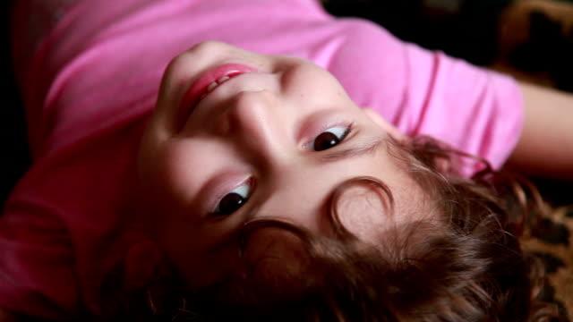 vídeos de stock e filmes b-roll de close-up of a happy little girl lying on the back and looking at camera - só uma rapariga