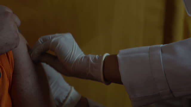 close-up of a health worker's hand administers a dose of covishield, the local name for the covid-19 vaccine developed by astrazeneca plc. and the... - human arm stock videos & royalty-free footage