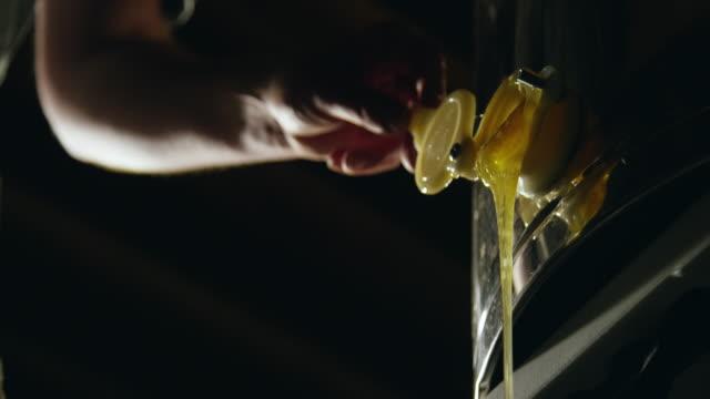 vídeos y material grabado en eventos de stock de primer plano de una mano humana abriendo un spigot con miel goteando - miel
