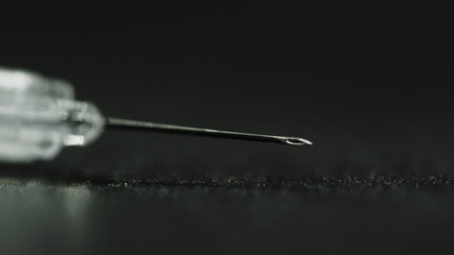 close-up of a hypodermic syringe's sharp needle sitting on a black table - syringe stock videos & royalty-free footage