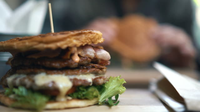 Closeup of a juicy burger and a person in background eating.