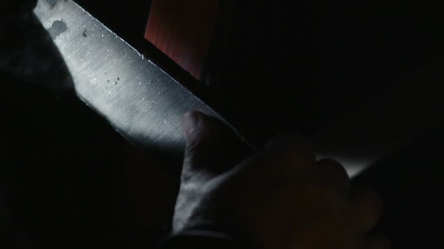 Close-up of a knife blade being sanded in a blacksmithing workshop.