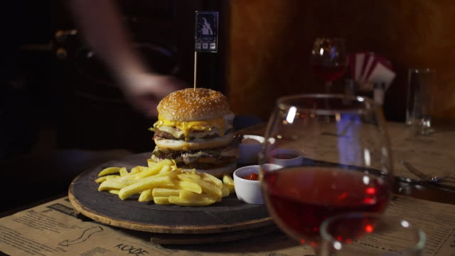 closeup of a large cheeseburger being prepared and served with ketchup being added - cheeseburger stock videos & royalty-free footage