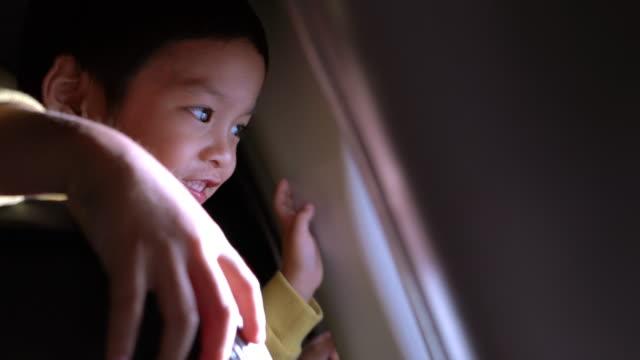 nahaufnahme eines kleinen asiatischen jungen, der aus dem fenster des flugzeugs schaut - passagierflugzeug stock-videos und b-roll-filmmaterial