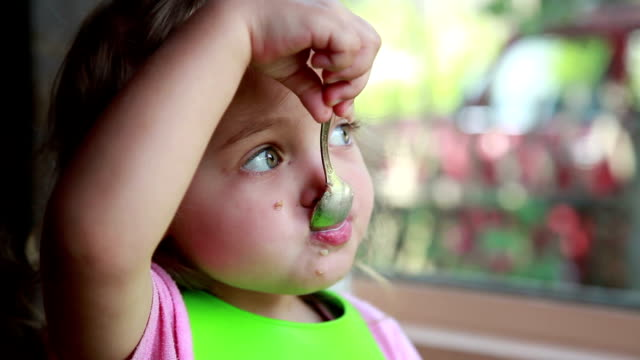 vidéos et rushes de plan rapproché d'une petite fille mangeant le petit déjeuner devant la fenêtre - 2 3 ans