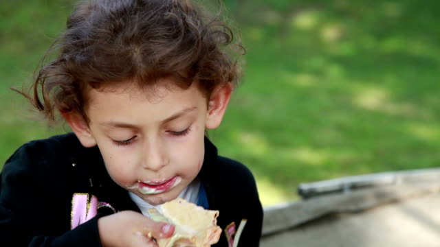close-up of a little girl eating ice cream in the park - messy stock videos & royalty-free footage