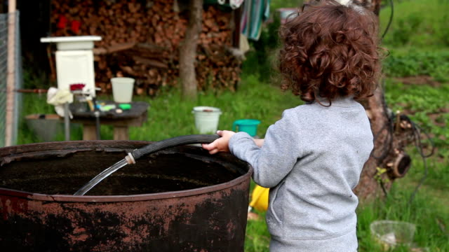 close-up of a little girl filling up the metal barrel with water - profilo vista laterale video stock e b–roll
