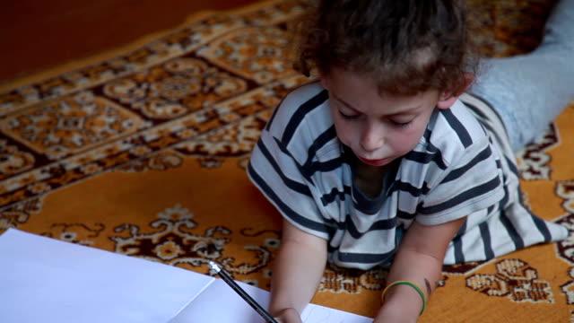 vidéos et rushes de plan rapproché d'une petite fille se trouvant sur le tapis dans le salon et dessinant avec des crayons - se mordre les lèvres