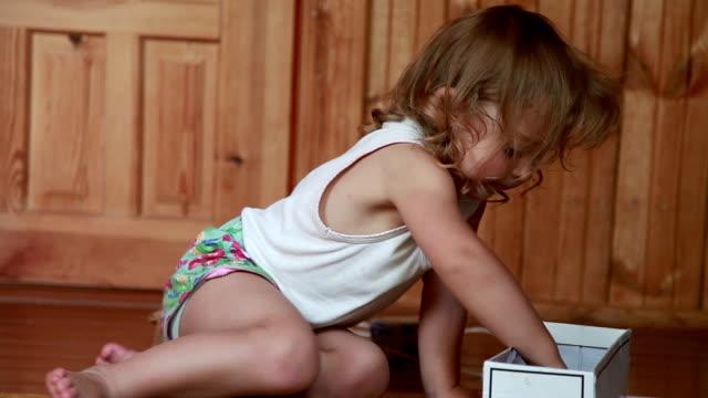リビングルームでおもちゃで遊ぶ小さな女の子のクローズアップ - all shirts点の映像素材/bロール