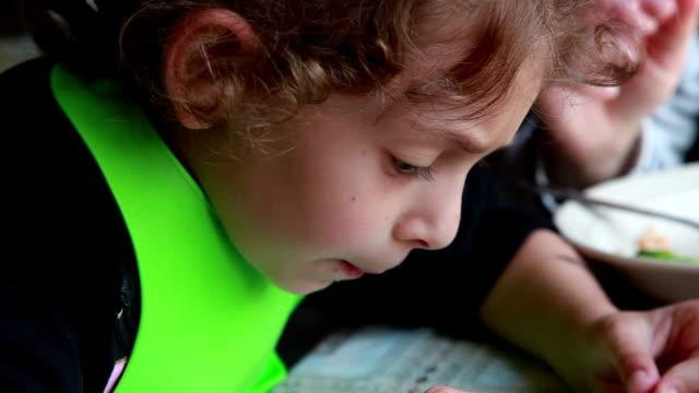 台所で本を読む小さな女の子のクローズアップ - 横顔点の映像素材/bロール
