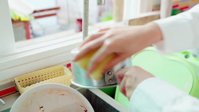 closeup of a maid washing dishes or doing housework. - cleaning sponge stock videos & royalty-free footage