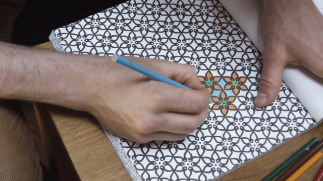 A closeup of a man coloring in an adult coloring book.