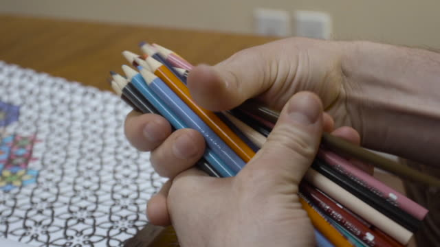 a closeup of a man deciding which color pencil to use in his adult coloring book. - colored pencil stock videos and b-roll footage