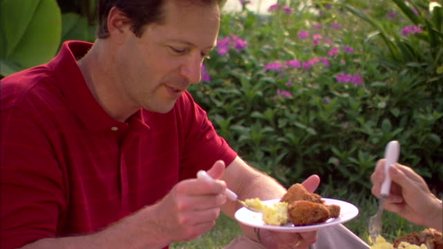 close-up of a man enjoying potato salad and fried chicken while on a picnic. - fried potato stock videos and b-roll footage