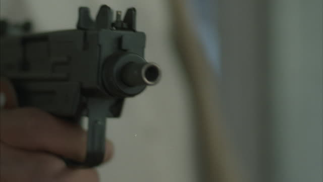 close-up of a man firing a black uzi handgun. - machine gun stock videos & royalty-free footage