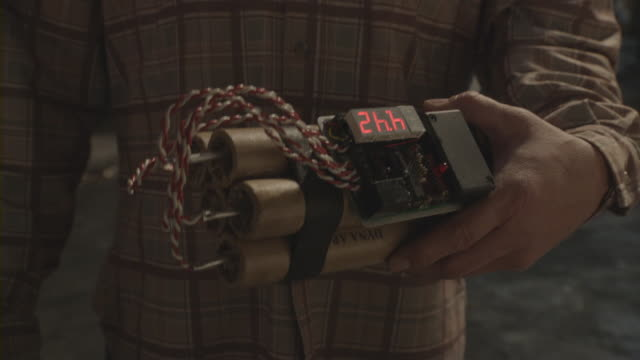 Close-up of a man holding a bomb with a countdown timer.