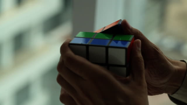 stockvideo's en b-roll-footage met close-up of a man playing with puzzle  - puzzel