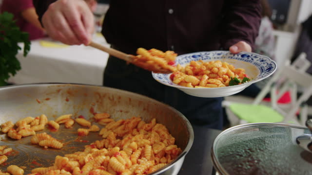 close-up of a man serving himself pasta at buffet lunch - pasta video stock e b–roll