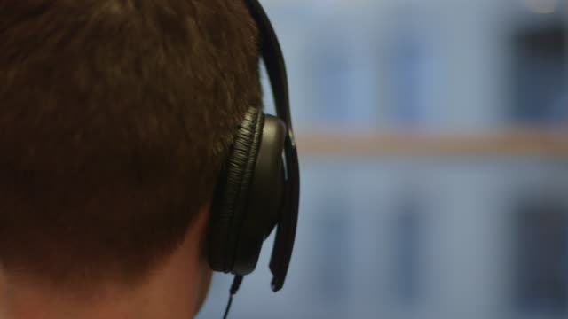 close-up of a man standing in front of a window listening to music through headphones, uk. - headphones stock videos & royalty-free footage