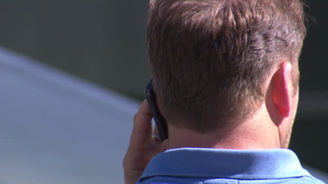 close-up of a man talking into a mobile phone on a sunny day, uk. - telecommunications equipment stock videos & royalty-free footage