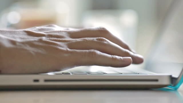Close-up of a man typing on a laptop keyboard