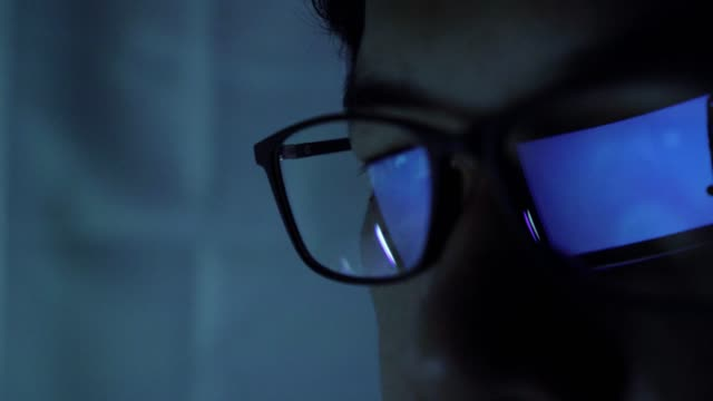 close-up of a man using a computer focus through glasses - lens eye stock videos & royalty-free footage