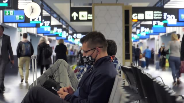 closeup of a man wearing a facemask in the terminal of vienna airport passengers wearing facemasks face shields gloves and other safety measures are... - flughafen stock videos & royalty-free footage