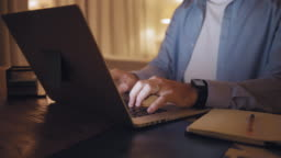 Close-up of a man working from home typing on laptop till late night