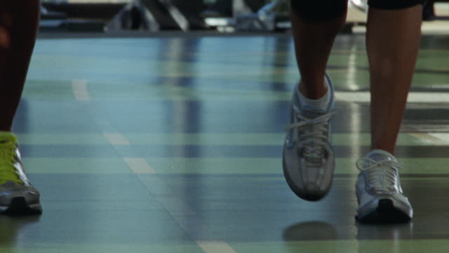 Closeup of a man's and a woman's legs and feet, on the walking track at a fitness gym.