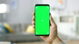 Close-up of a Man's Hand Holding Green Mock-up Screen Smartphone. Modern Mobile Phone. In the Background Cozy Living Room or Home Office.
