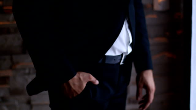 Close-up of a man's hand in his suit pocket