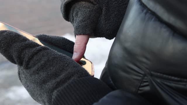 vídeos de stock, filmes e b-roll de close-up das mãos de um homem jogando no inverno no telefone amóvel em um vídeo de resolução 4k - inverno