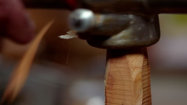 close-up of a manual metal tool being twisted over wood to create a spindle shape in a workshop. - wood material stock videos & royalty-free footage