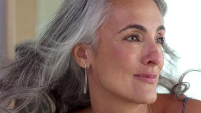 vidéos et rushes de close-up of a middle-aged woman with gray hair smiling as hair blows from wind, against blurred background. - femme mure