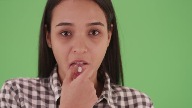 close-up of a millennial latina take a pill in plaid on green screen - plaid stock videos and b-roll footage