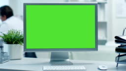 Close-up of a Monitor with Green Screen. Doctor Working at his Desk in the Background. Shot in a Modern Medical Office.