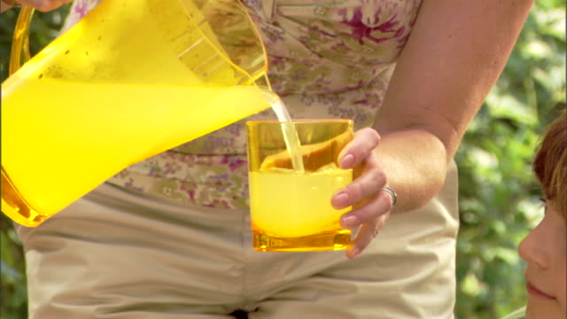 close-up of a mother pouring lemonade in a glass. - bricco video stock e b–roll