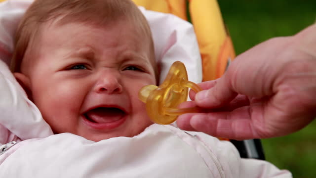 close-up of a mothers hand giving pacifier to a baby - giving stock videos & royalty-free footage
