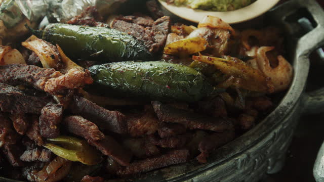 vídeos de stock e filmes b-roll de a closeup of a mouthwatering platter of beef fajitas, with sauteed onion and peppers topped with two roasted chili peppers with a side of guacamole, limes and hot fresh corn tortillas - modo de preparação de comida