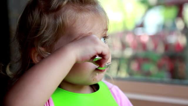 vidéos et rushes de plan rapproché d'une petite fille pensive mangeant le petit déjeuner - céréale