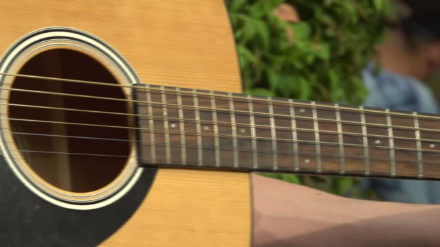close-up of a person playing an acoustic guitar - アコースティックギター点の映像素材/bロール