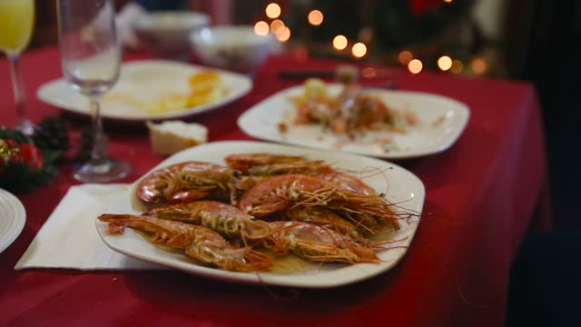 close-up of a plate of prawns that a hand reaches and places on the family christmas table with the bokeh of christmas tree lights behind - テナガエビ点の映像素材/bロール