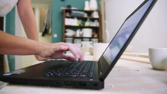 nahaufnahme eines töpferhandwerkers, der seine online-bestellungen überprüft - wissenschaft und technik stock-videos und b-roll-filmmaterial