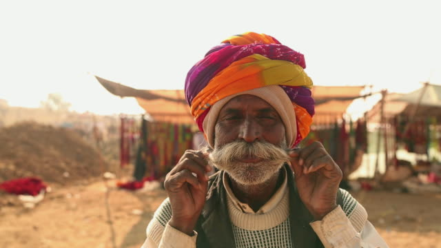 close-up of a rajasthani senior man adjusting his moustache, pushkar, rajasthan, india - barba peluria del viso video stock e b–roll