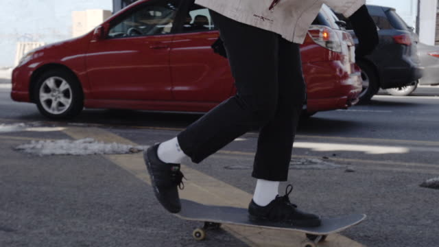 Closeup of a real person skateboarding through the streets of Brooklyn, NYC - female - african american
