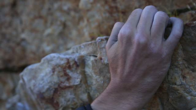 close-up of a rock climbers hand as he grips the mountainside. - rock climbing stock videos & royalty-free footage