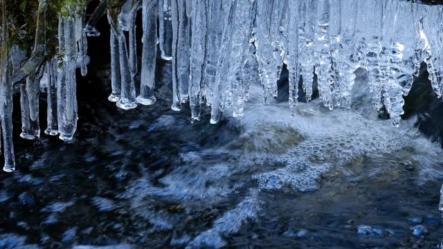 close-up of a running water and ice in a stream in the spring in clear light - rapid stock videos & royalty-free footage