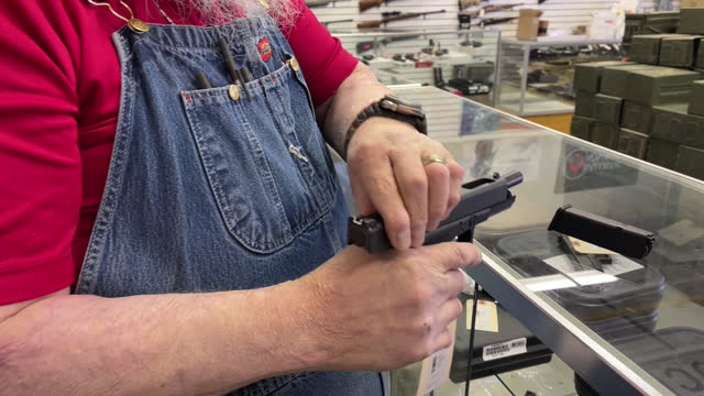 close-up of a salesman taking a glock handgun out of a case at a store in orem, utah, u.s. on thursday, march 25, 2021 . sales and orders of ar-15s... - orem utah stock videos & royalty-free footage