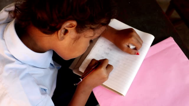 Close-up of a schoolgirl writing on notebook, Haryana, India